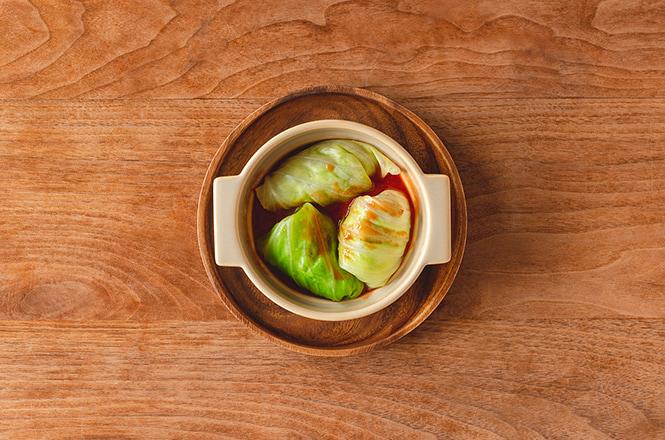 合挽肉と玉ねぎ、調味料を混ぜ合わせたものをキャベツで包み、オーブン皿に敷き詰めます